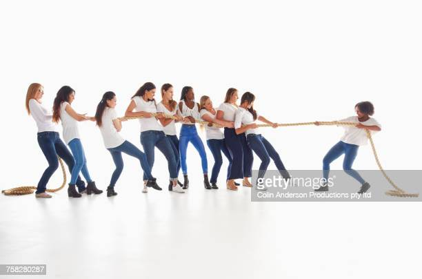 diverse women playing tug-of-war - unfairness stock pictures, royalty-free photos & images