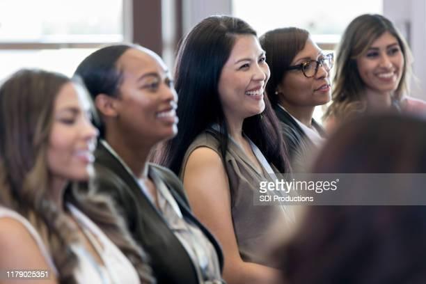 as mulheres diversas sentam-se na fileira que escuta o apresentador invisível - diverse women - fotografias e filmes do acervo