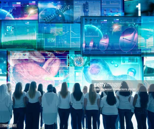 Diverse women watching large visual screens