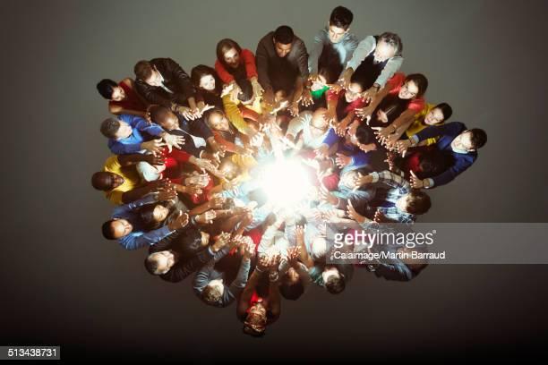 Diverse workers around bright light