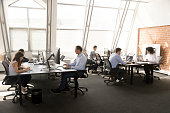 Diverse workers sitting at desk working in coworking space