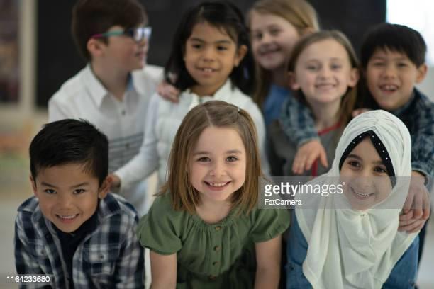 os colegas novos diversos huddled junto para um retrato de sorriso - hijab - fotografias e filmes do acervo