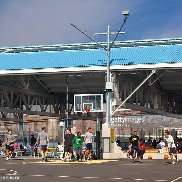 Diverse Junge Männer spielen Basketball, Brooklyn Bridge Park, New York.