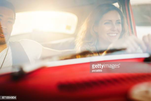 Diversity: multiethnic couple in a red vintage car