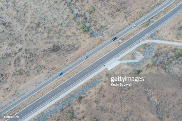 A divided highway runs through the North Phoenix desert with 4 vehicles aerial image from a hot air balloon