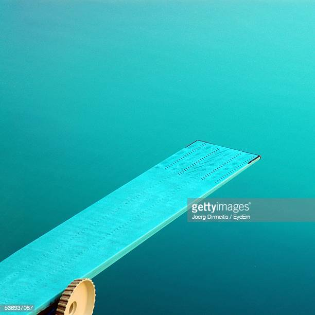 Diving Board Against Turquoise Swimming Pool