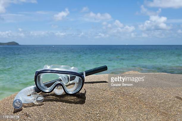 a diving mask and snorkel on a rock near the sea - scuba mask stock pictures, royalty-free photos & images