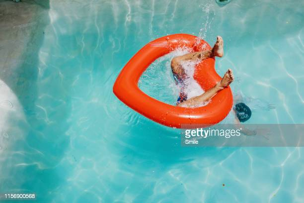 diving through heart-shaped inflatable into clear pool - pool party stock pictures, royalty-free photos & images