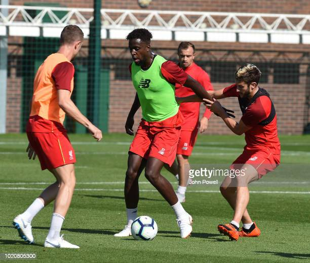 Divock Origi and Adam Lallana of Liverpool during a training session at Melwood Training Ground on August 21 2018 in Liverpool England