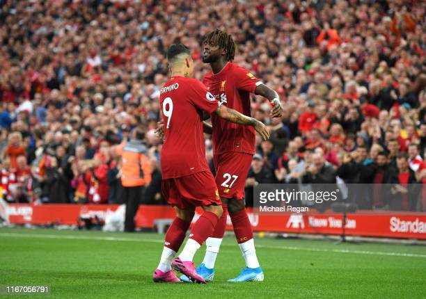 Divock Origi and Roberto Firmino of Liverpool celebrates after Grant Hanley of Norwich City scores an own goal during the Premier League match...