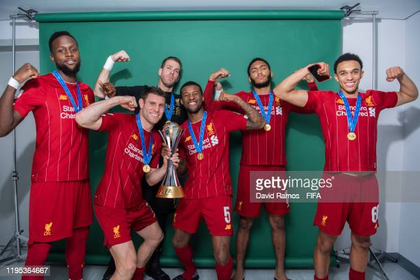 Divock Origi, James Milner, Adrian, Georginio Wijnaldum, Joseph Gomez and Trent Alexander-Arnold of Liverpool pose with the Club World Cup trophy...
