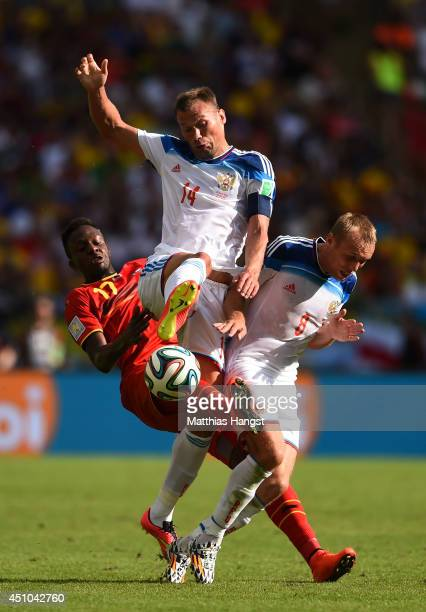 Divock Origi of Belgium, Vasily Berezutskiy and Denis Glushakov of Russia clash during the 2014 FIFA World Cup Brazil Group H match between Belgium...