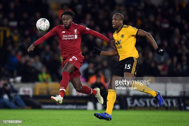 Divock Origi of Liverpool avoids Willy Boly during the Emirates FA Cup Third Round match between Wolverhampton Wanderers and Liverpool at Molineux on...