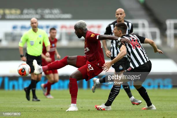 Divock Origi of Liverpool battles for possession with Federico Fernandez of Newcastle United during the Premier League match between Newcastle United...