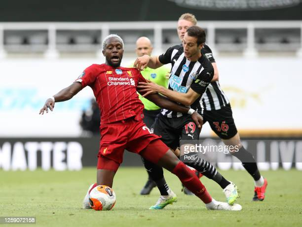 Divock Origi of Liverpool battles for possession with Javier Manquillo of Newcastle United during the Premier League match between Newcastle United...