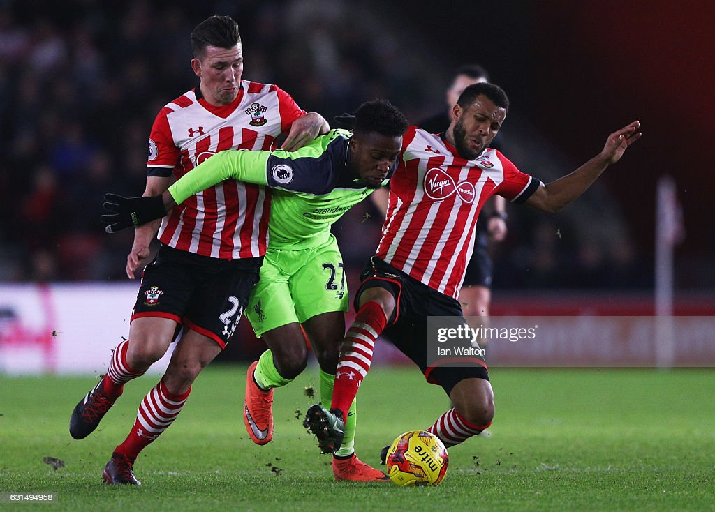 Divock Origi of Liverpool battles with Pierre-Emile Hojbjerg (L) and Ryan Bertrand of Southampton during the EFL Cup semi-final first leg match between Southampton and Liverpool at St Mary's Stadium on January 11, 2017 in Southampton, England.