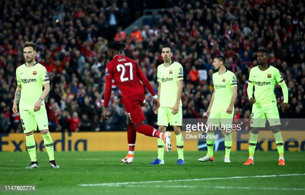 Divock Origi of Liverpool celebrates after he scores his team's fourth goal as the Barcelona defence look on dejected during the UEFA Champions...
