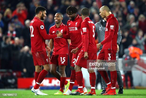 Divock Origi of Liverpool celebrates his team's victory with teammate Joe Gomez after the Premier League match between Liverpool FC and Everton FC at...