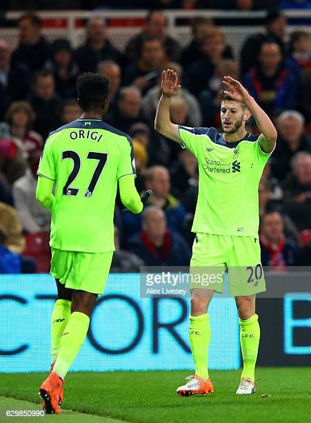 Divock Origi of Liverpool celebrates scoring his team's second goal with his team mate Adam Lallana during the Premier League match between...