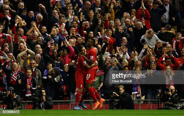 Divock Origi of Liverpool celebrates with Roberto Firminho after scoring the opening goal during the Barclays Premier League match between Liverpool...