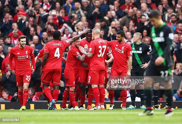 Divock Origi of Liverpool celebrates with team mates as he scores their fourth goal during the Barclays Premier League match between Liverpool and...