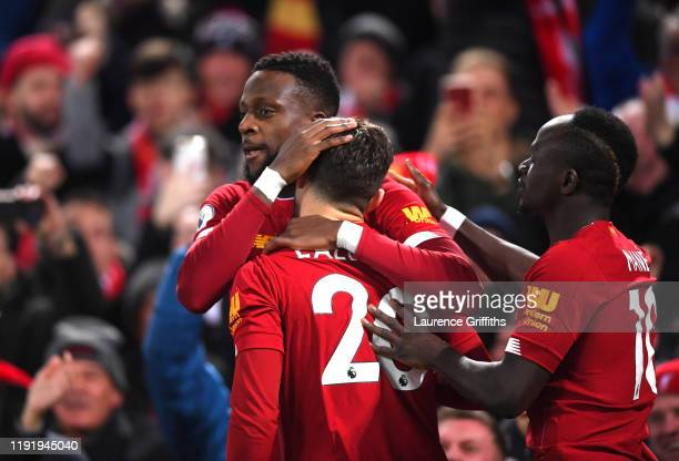 Divock Origi of Liverpool celebrates with teammate Adam Lallana after scoring his team's first goal during the Premier League match between Liverpool...