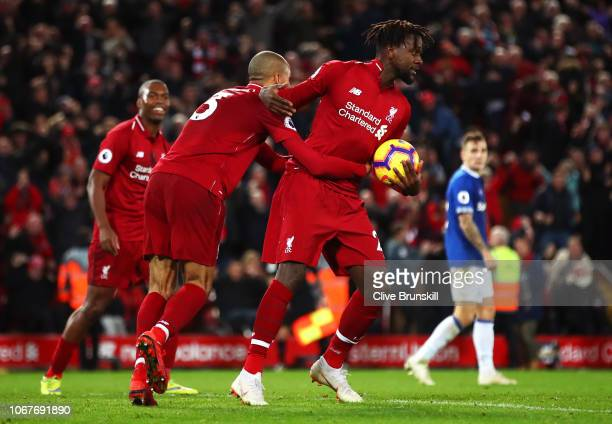 Divock Origi of Liverpool celebrates with teammate Fabinho after scoring his team's first goal during the Premier League match between Liverpool FC...
