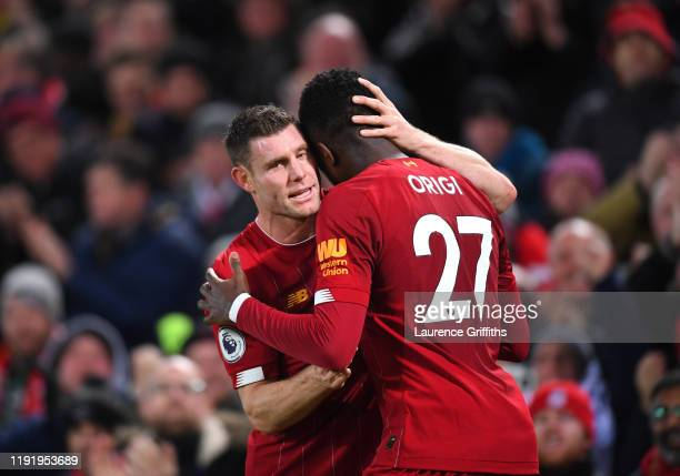 Divock Origi of Liverpool celebrates with teammate James Milner after scoring his team's third goal during the Premier League match between Liverpool...