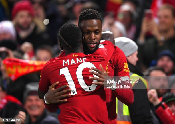 Divock Origi of Liverpool celebrates with teammate Sadio Mane after scoring his team's first goal during the Premier League match between Liverpool...