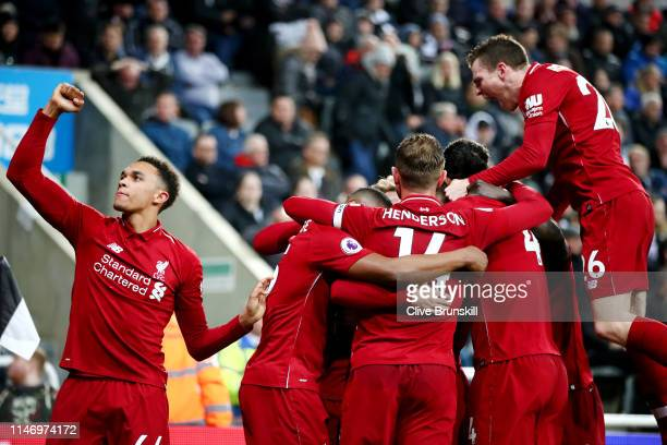 Divock Origi of Liverpool celebrates with teammates after scoring his team's third goal during the Premier League match between Newcastle United and...