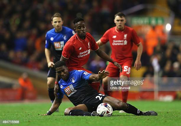Divock Origi of Liverpool challenges Sylvain Distin of Bournemouth during the Capital One Cup Fourth Round match between Liverpool and AFC...