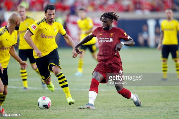 Divock Origi of Liverpool FC controls the ball ahead of Mats Hummels of Borussia Dortmund in the first half of the preseason friendly match at Notre...