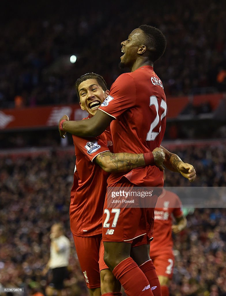 Divock Origi of Liverpool is congratulated by Roberto Firmino after his goal during the Barclays Premier League match between Liverpool and Everton at Anfield on April 20, 2016 in Liverpool, England