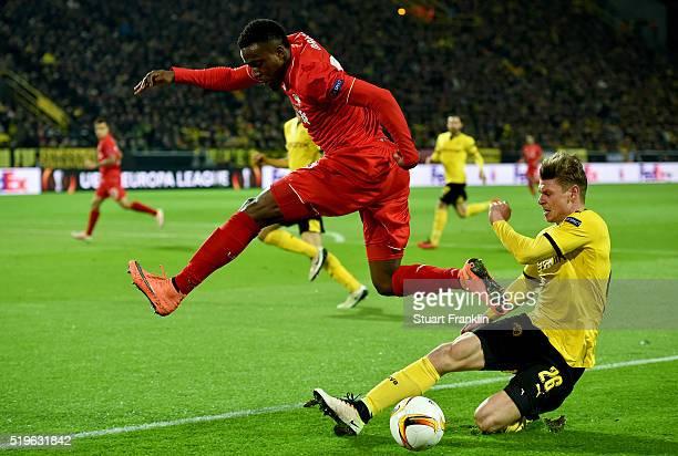 Divock Origi of Liverpool is tackled by Lukasz Piszczek of Borussia Dortmund during the UEFA Europa League quarter final first leg match between...