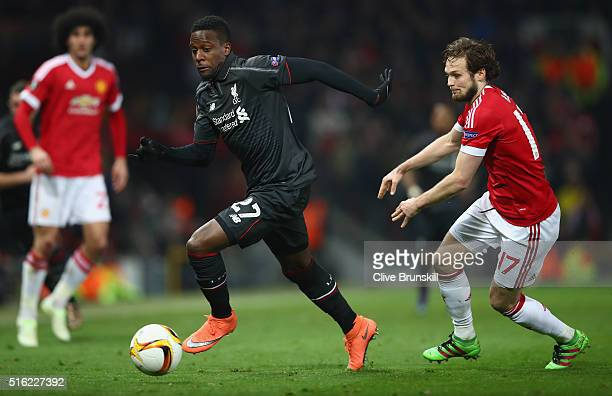 Divock Origi of Liverpool moves away from Daley Blind of Manchester United during the UEFA Europa League round of 16 second leg match between...