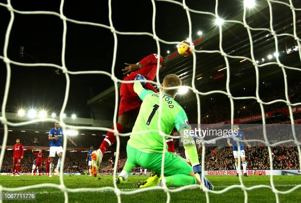 Divock Origi of Liverpool scores his team's first goal past Jordan Pickford of Everton during the Premier League match between Liverpool FC and...