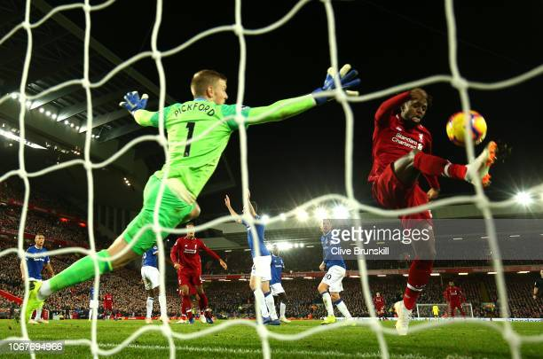 Divock Origi of Liverpool shoots and misses as Jordan Pickford of Everton reaches for the ball during the Premier League match between Liverpool FC...