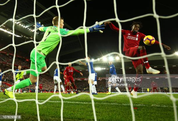 Divock Origi of Liverpool shoots and misses hitting the crossbar as Jordan Pickford of Everton reaches for the ball during the Premier League match...