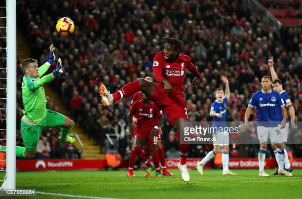 Divock Origi of Liverpool shoots under pressure from Jordan Pickford of Everton during the Premier League match between Liverpool FC and Everton FC...