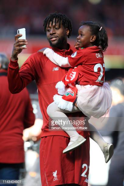 Divock Origi of Liverpool takes a selfie with his mobile phone with his daughter after the Premier League match between Liverpool and Wolverhampton...