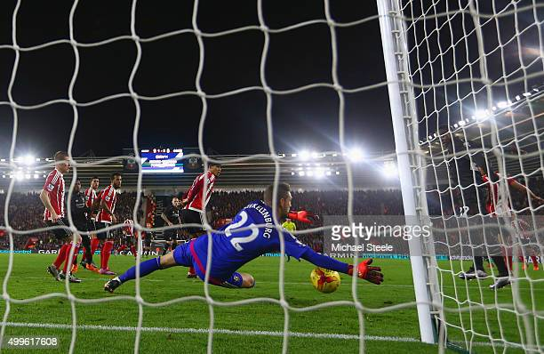 Divock Origi of Liverpool touches the ball past goalkeeper Maarten Stekelenburg of Southampton to score their third goal during the Capital One Cup...