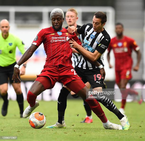 Divock Origi of Liverpool with Newcastles Javier Manquillo during the Premier League match between Newcastle United and Liverpool FC at St James Park...