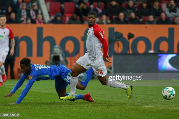 Divock Origi of Wolfsburg and Kevin Danso of Augsburg battle for the ball during the Bundesliga match between FC Augsburg and VfL Wolfsburg at...
