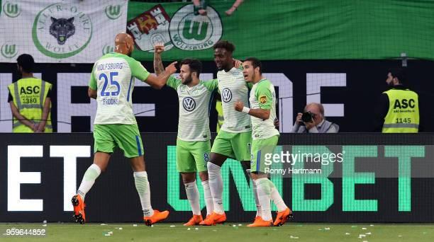 Divock Origi of Wolfsburg celebrates after scoring his team's opening goal with John Anthony Brooks Renato Steffen and William during the Bundesliga...