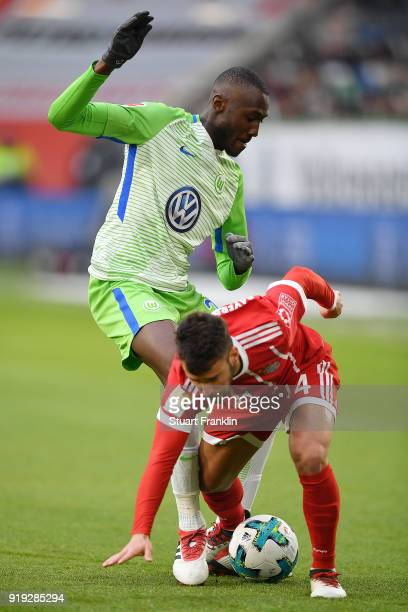 Divock Origi of Wolfsburg fights for the ball with Tolisso of Bayern Muenchen during the Bundesliga match between VfL Wolfsburg and FC Bayern...