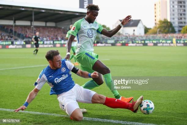Divock Origi of Wolfsburg is challenged by Rafael Czichos of Kiel during the Bundesliga Playoff Leg 2 match between Holstein Kiel and VfL Wolfsburg...
