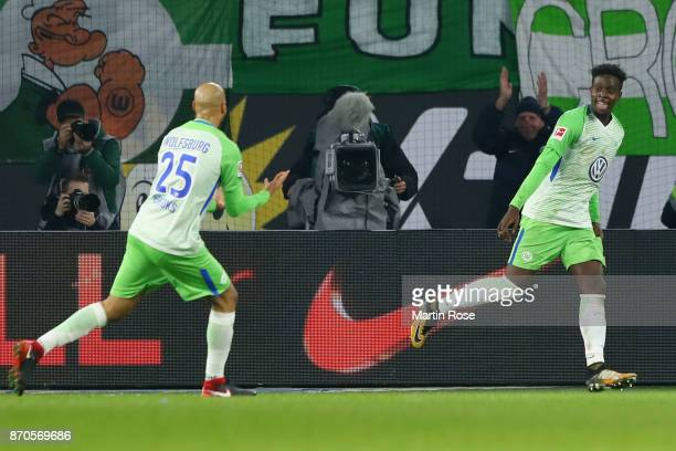 Divock Origi R of Wolfsburg celebrates his team's third goal with team mate John Anthony Brooks during the Bundesliga match between VfL Wolfsburg and...