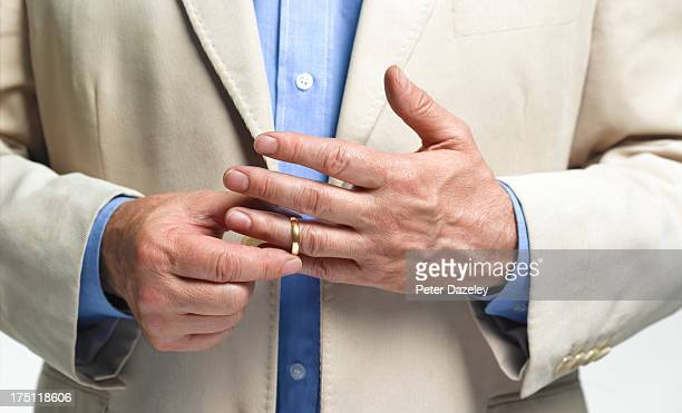 Divorced man taking off wedding ring