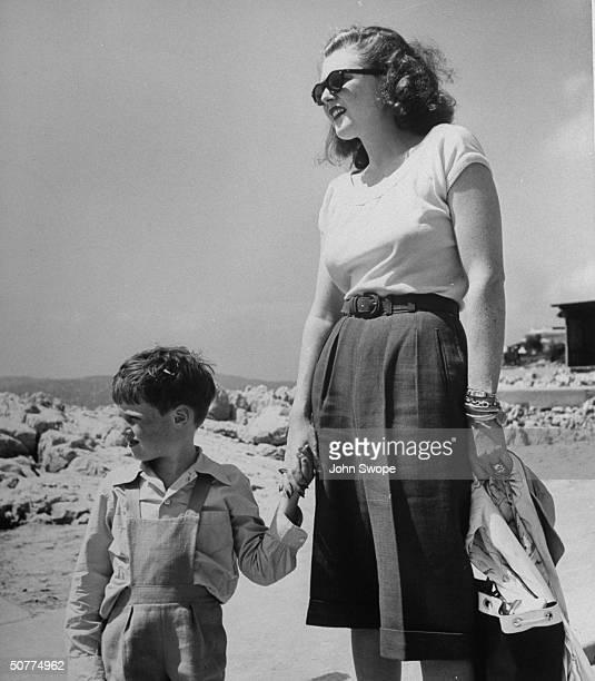 Divorced wife of Randolph Churchill, Pamela, in slacks, with small son Winston Churchill II, at Eden Roc.