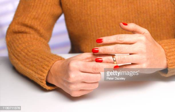 divorced woman taking off wedding ring - separation stock pictures, royalty-free photos & images